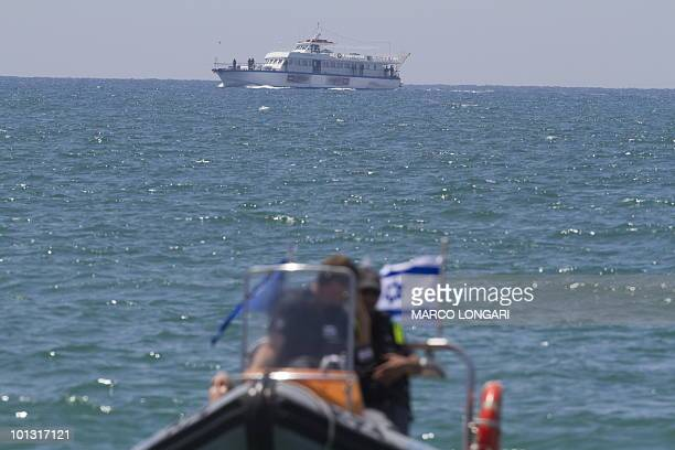 An Israeli police patrol boat stands by as a boat enters the northern entrance of the Israeli port of Ashdod on May 31 following the storming by...