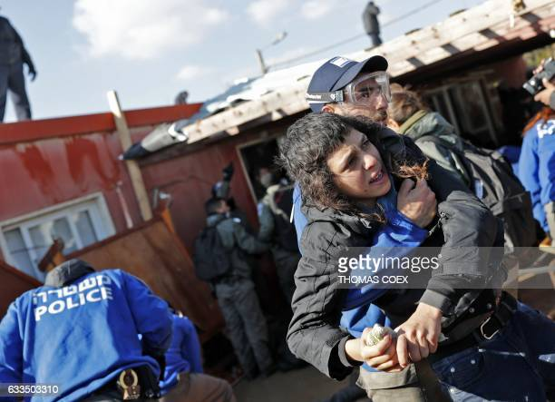 An Israeli policeman carries a young Israeli settler on the second day of an operation to evict the hardline occupants and their supporters from the...