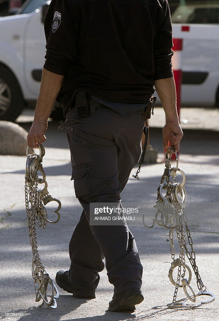 An Israeli policeman carry handcuffs near a demonstration of supporters of Samer al-Issawi, a Palestinian prisoner who is on a hunger strike, that takes place outside the Magistrate's Court which rules on Issawi's case, on February 21, 2013 in Jerusalem. Issawi, who comes from annexed east Jerusalem, was released under terms of the 2011 prisoner swap deal and was rearrested in July on charges of violating the terms of his release by taking his car to a garage in the West Bank.