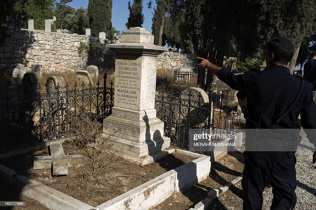 An Israeli policeman inspects a vandalized tombstone at a Christian cemetery located in mount Zion, outside Jerusalem's Old City on September 29, 2013. Police caught four young Israelis red-handed as they vandalized 15 Christian tombstones in the graveyard near the Old City of the holy city.