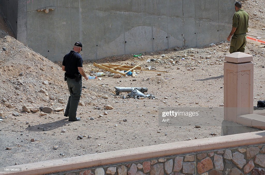 An Israeli policeman inspects the site of a rocket explosion in the Israeli Red Sea resort of Eilat April 17 2013. A Salafi jihadist group claimed responsibility for firing what it said were Grad rockets at Eilat, causing no damage or casualties. AFP PHOTO/NOA ELIYAHU ==ISRAEL OUT==