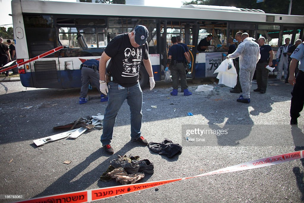 An Israeli policeman stands above shoes and clothes of a victim at the scene of an explosion on a bus with passengers onboard on November 21, 2012 in central Tel Aviv, Israel. At least ten people have been injured in a blast on a bus near military headquarters in what is being described as terrorist attack, which threatens to derail ongoing cease-fire negotiations between Israeli and Palestinian authorities.