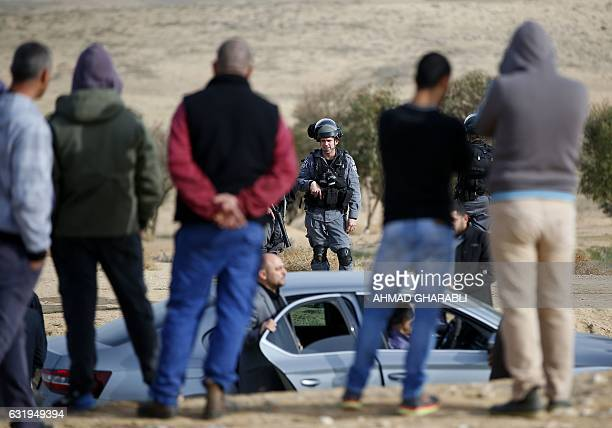 An Israeli policeman stands facing ArabIsraeli protestors in the Bedouin village of Umm alHiran which is not recognized by the Israeli government...