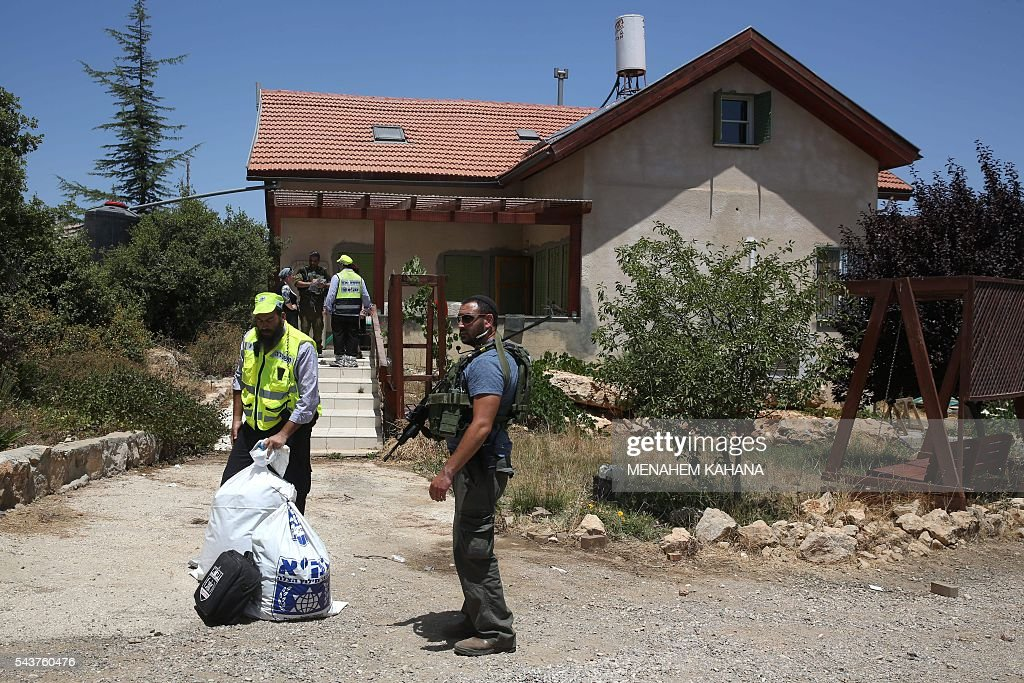 An Israeli policeman stands guard as Zaka volunteers, an emergency response team in Israel, collect human remains in a house in the Jewish settlement of Kiryat Arba in the occupied West Bank where a 13-year-old Israeli girl was fatally stabbed in her bedroom on June 30, 2016. A Palestinian attacker stabbed a 13-year-old girl to death at her home in the Jewish settlement outside the city of Hebron before being shot dead by security guards, the Israeli army said. KAHANA