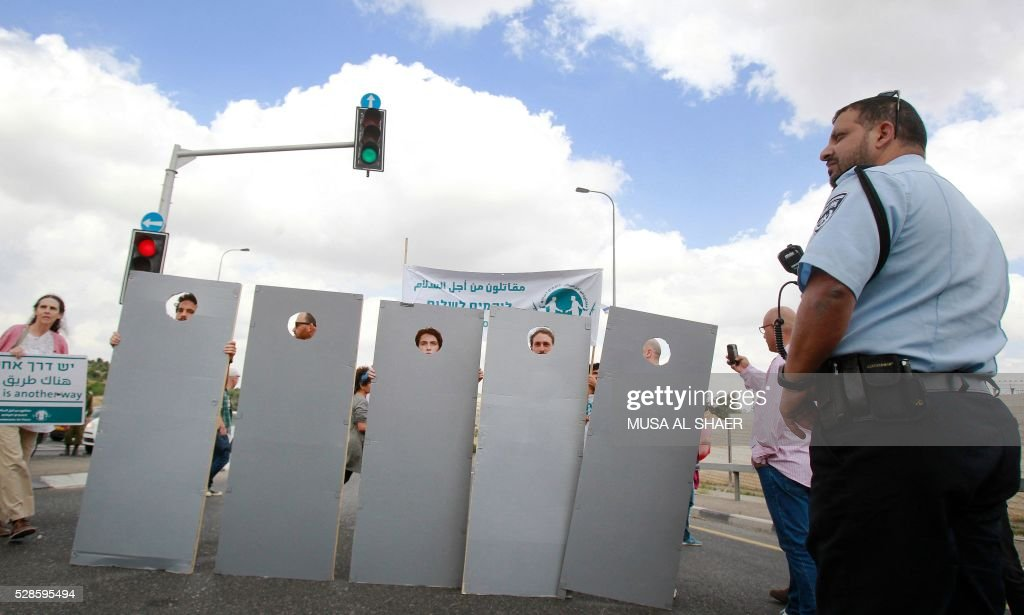 An Israeli Police man stands guard opposite to Israeli and Palestinian peace activists walking behind cardboard cut-outs depicting the Israeli controversial separation wall during a peace march at an Israeli road near a checkpoint between the West Bank city of Beit Jala and Jerusalem, on May 6, 2016. / AFP / MUSA