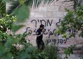 An Israeli policeman walks past graffiti on the wall of a church reading in Hebrew 'King David king of the Jews and Jesus is garbage Price tag' on...