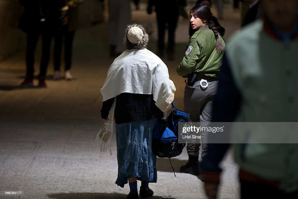An Israeli policewoman detains a member of the religious group 'Women of the Wall' wearing a 'Tallit' (traditional Jewish prayer shawl) during a prayer marking the first day of the Jewish month of Iyar at the Western Wall on April 11, 2013 in Jerusalem's Old City, Israel. Five members of the organisation 'Women of the Wall' were detained by police during the group's monthly prayer at the Western Wall, after covering themselves with prayer shawls in contradiction to the holy site's custom.
