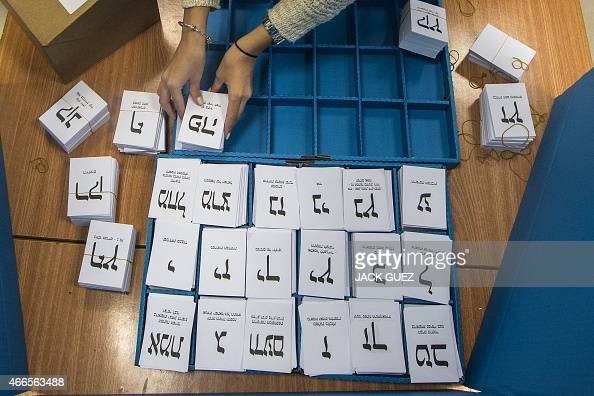 An Israeli polling station worker arranges ballots during Israel's general elections on March 17 2015 in the coastal city of Haifa Voting polls...