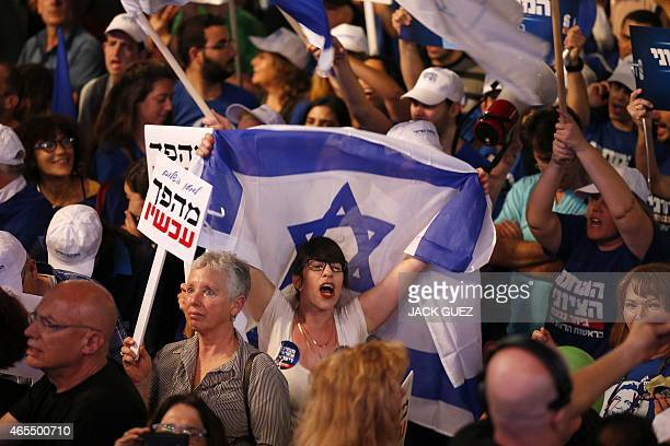 An Israeli protester waves a national flag during a rally to ask for a change in the Israeli policy on March 7 2015 on Rabin Square in the Israeli...