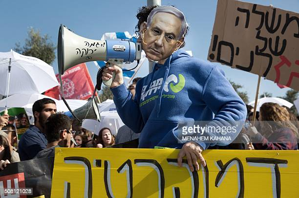 TOPSHOT An Israeli protester wears a mask bearing a portrait of Prime Minister Benjamin Netanyahu during a protest on February 3 2016 in front of the...