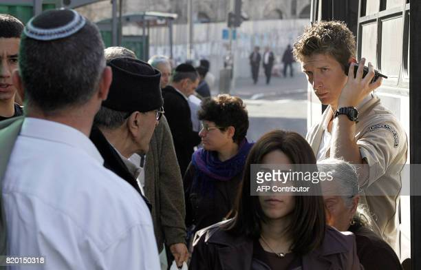 An Israeli public transportation security officer listens to a message as he stands guard at a bus stop close to a local market in central Jerusalem...