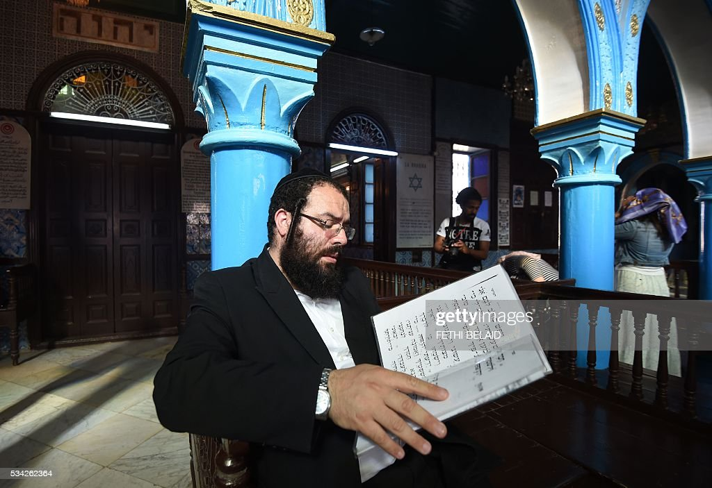 An Israeli rabbi reads the Torah, Judaisms most important text, at the Ghriba synagogue on the Tunisian resort island of Djerba during the annual Jewish pilgrimage on May 25, 2016. Pilgrims arrived at Tunisia's Ghriba synagogue, the oldest in Africa, expressing hope that this year would mark a turning point for the ritual despite a rise in Islamist unrest since the 2011 revolution. Djerba is home to one of the last Jewish communities in the Arab world. / AFP / FETHI