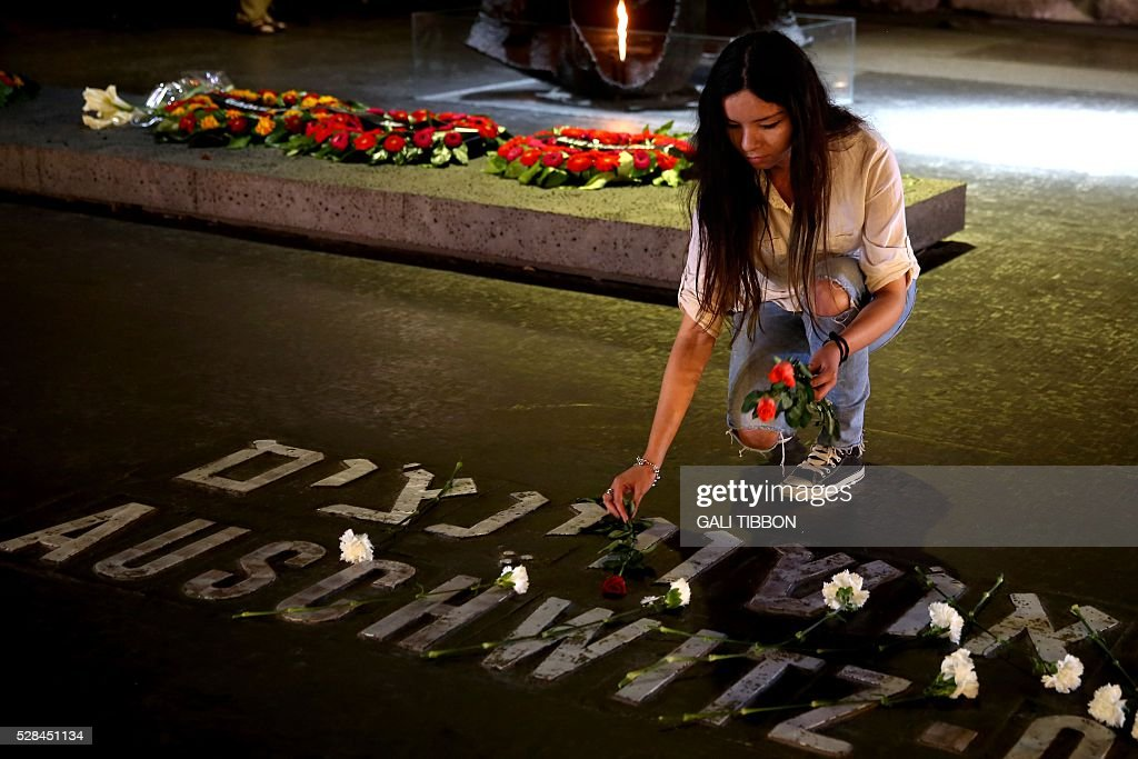 An Israeli relative of Holocaust victims lays a flower at the Hall of Remembrance where the names of major death and concentration camps are written during a ceremony marking the annual Holocaust Remembrance Day at the Yad Vashem Holocaust Memorial in Jerusalem on May 5, 2016. The state of Israel marks the annual Memorial Day commemorating the six million Jews murdered by the Nazis in the Holocaust during World War II. / AFP / GALI