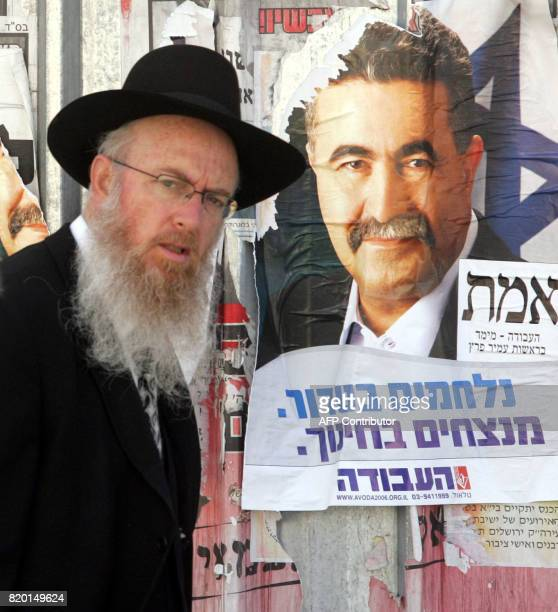 An Israeli religious man walks past an election poster of Amir Peretz the leader of the Labour party as he walks in a district of Jerusalem 22 March...