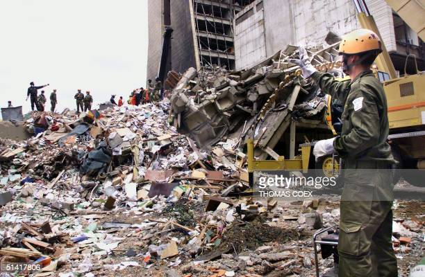An Israeli rescue worker calls to colleagues 10 August as they stand on what remains of a building in front of the US embassy in Nairobi four days...