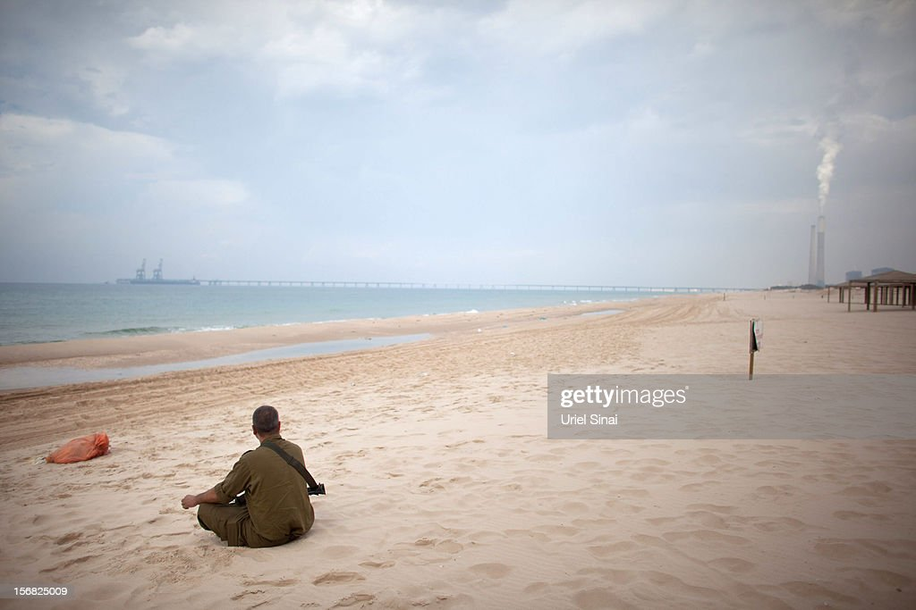 An Israeli reserve soldier sits on the beach as he prepares leaves the Gaza border area on November 22, 2012 near Israel's border with the Gaza Strip. The ceasefire between Israel and Hamas appears to be holding despite rockets being fired from Gaza. During the night the IDF reportedly arrested a number of 'terror operatives' in the West Bank in continued efforts to restore peace in the region.