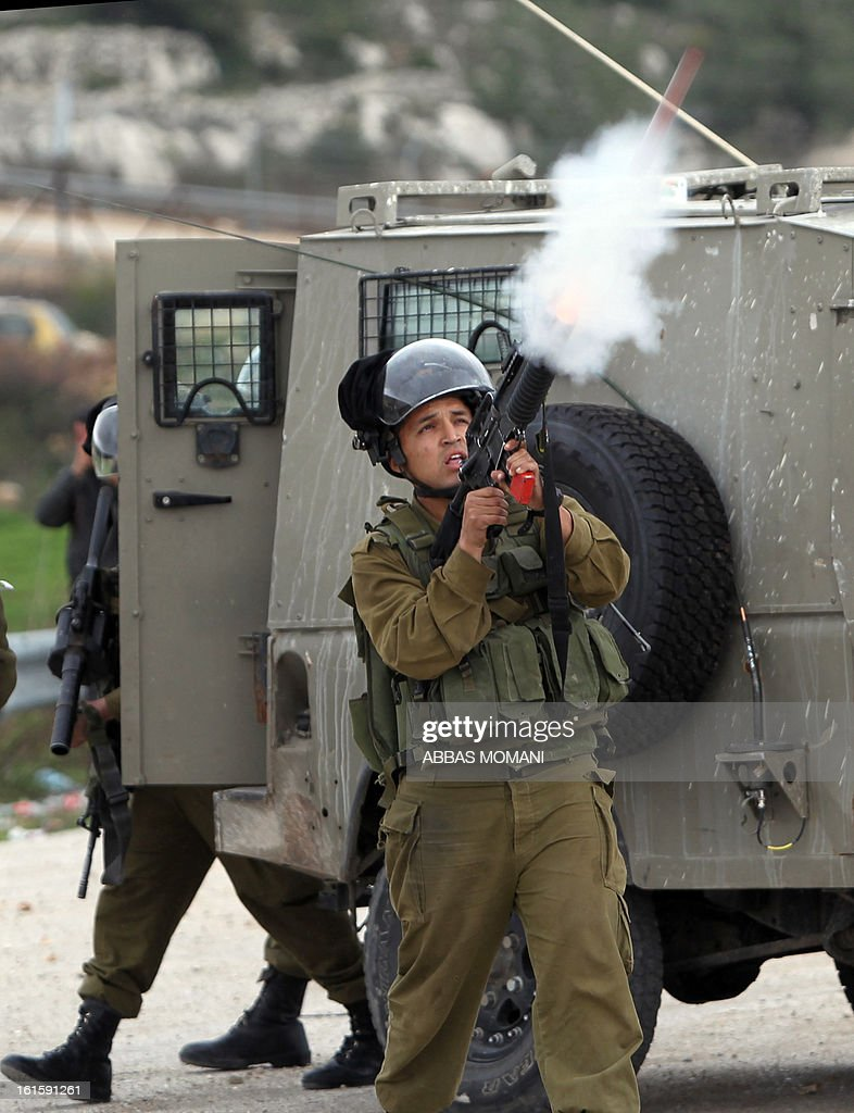An Israeli security fires a smoke grenade at students from the University of Birzeit during clashes outside Israel's Ofer military prison, near the West Bank city of Ramallah, on February 12, 2013, following a demonstration in support of Palestinian prisoners on hunger strike in Israeli jails.