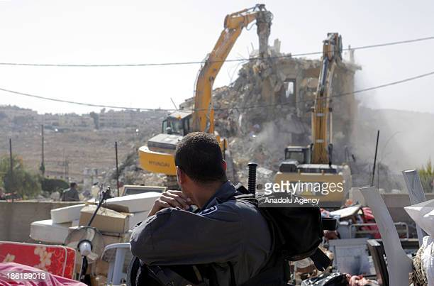 An Israeli security force member keeps guard as Israeli bulldozers demolish a fourstorey house owned by a Palestinian on the grounds that the house...