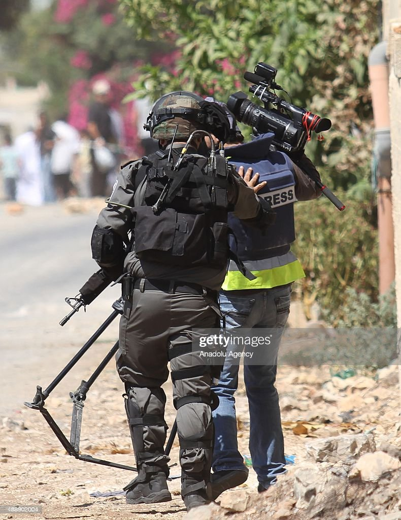 An Israeli security forces member pushes a press member during the clashes following a protest against Israeli Government's violation over AlAqsa...