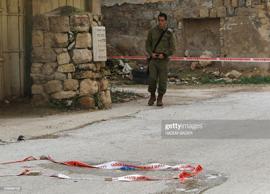 An Israeli security forces members monitors the site where a Palestinian woman tried to stab an Israeli soldier before being shot dead, in the Israeli occupied West Bank city of Hebron, on February 13, 2016. An Israeli army statement said that 'An assailant drew a knife and attempted to stab a soldier,', 'Responding to the attack, forces fired at the perpetrator, resulting in her death.' The Palestinian health ministry confirmed that a woman was killed but could not immediately give her age or name. The army statement said that the incident occurred near Hebron's shared religious site known to Jews as the Cave of the Patriarchs and to Muslims as the Ibrahimi Mosque, a site of frequent friction between the sides. BADER