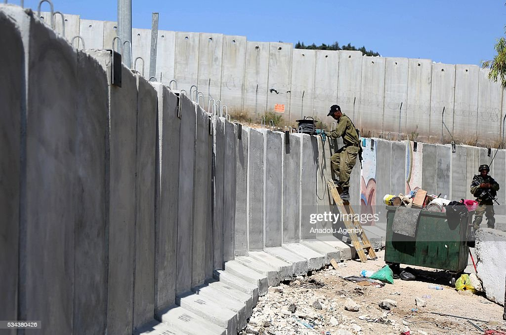 An Israeli security guard climbs the concrete wall as Israeli security forces increase the security measures around Hizma district of Jerusalem on May 26, 2016.