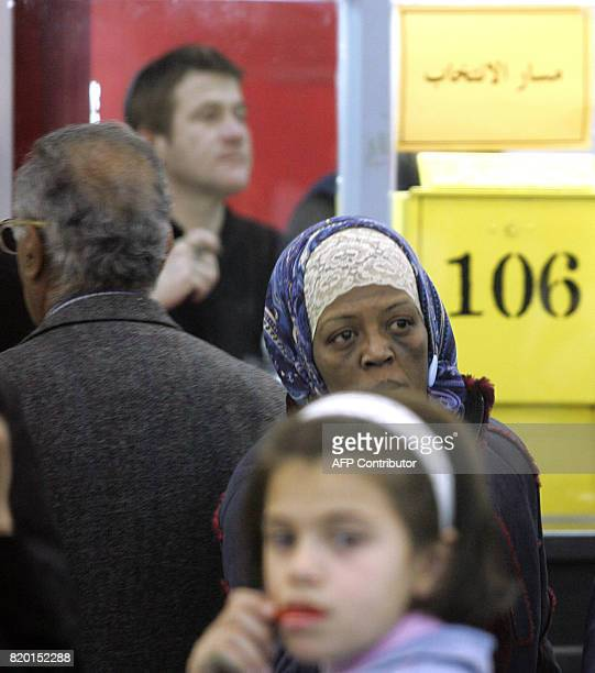 An israeli security officer stands guard as Palestinians queue at the Salahaldin Street post office polling station 25 January 2006 as they wait to...