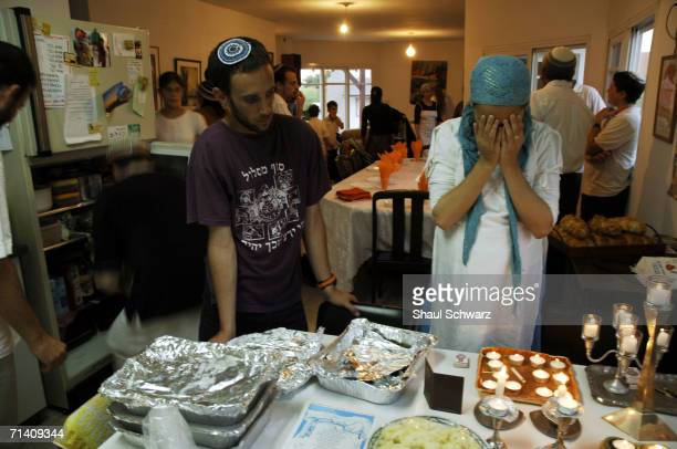 An Israeli settler covers her eyes in prayer as she lights traditional Jewish candles in honor of Shabbat at the house of the Golan family August 12...
