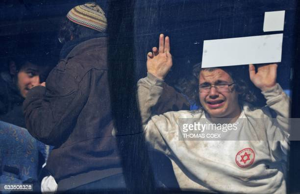 TOPSHOT An Israeli settler cries as he looks out from a bus after being evicted from the West Bank settler outpost of Amona on the second day of an...