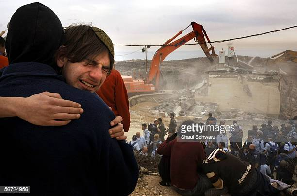 An Israeli settler cries in front of a building as it is destroyed by a backhoe on February 1 2006 in the West Bank outpost of Amona The residents of...