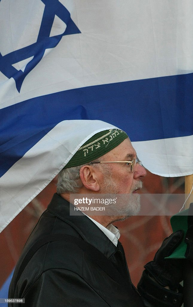 An Israeli settler from the Kiryat Arbaa and other Jewish settler zones, demonstrates in the West Bank city of Hebron, on Januray 15, 2013, calling for the return of houses and buildings which they say they bought from Palestinians in Hebron, a day after Israel's former top diplomat Avigdor Lieberman, who heads the hardline nationalist Yisrael Beitenu party, pre-election visit to the city's Tomb of the Patriarchs. Built over the spot where the biblical figure Abraham is believed buried, the Tomb of the Patriarchs is also known to Muslims as the Ibrahimi mosque.