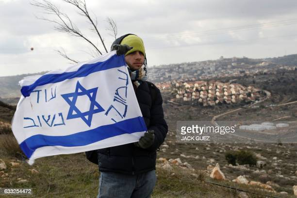 TOPSHOT An Israeli settler holds a flag with slogans at the Amona outpost northeast of Ramallah on February 1 2017 as Israeli security forces prepare...