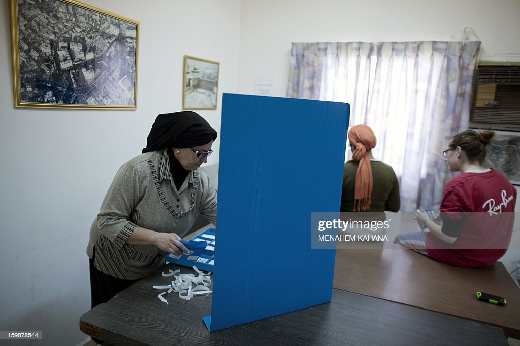 An Israeli settler marks her ballot behind a voting booth at a polling station in Maale Amos, part of the Jewish settlement bloc of Gush Etzion, in the West Bank on January 22, 2013. Voters across Israel and in settlements peppering the occupied West Bank cast ballots for the Israeli general election at more than 10,000 polling stations, with turnout standing at 38.3 percent after seven hours of voting.