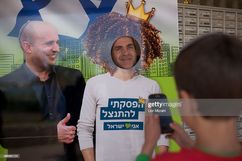 An Israeli settler poses for a picture next to a poster of leader of the Jewish Home party <a gi-track='captionPersonalityLinkClicked' href=/galleries/search?phrase=Naftali+Bennett&family=editorial&specificpeople=6632880 ng-click='$event.stopPropagation()'>Naftali Bennett</a> outside a polling station on election day on March 17, 2015 in the Jewish settelment of Ofra, West Bank. Israel's general election voting has begun today as polls show on that Chairman of the Zionist Union party, Isaac Herzog stands as the only rival to current Prime Minister Benjamin Netanyahu.
