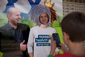 An Israeli settler poses for a picture next to a poster of leader of the Jewish Home party Naftali Bennett outside a polling station on election day...
