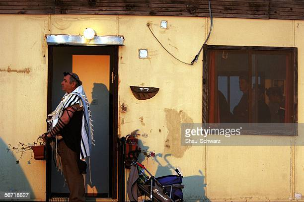 An Israeli settler prays at sunrise February 1 2006 in the West Bank outpost of Amona The residents of Amona compose one of eightyseven unauthorized...