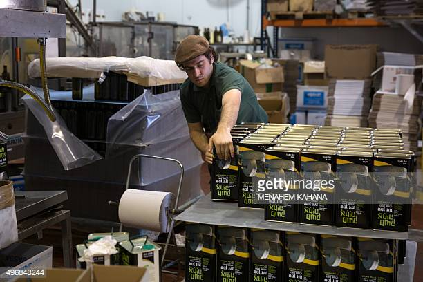 An Israeli settler prepares olive oil containers at the Achia Olive press factory in the Jewish settlement of Shilo in the occupied West Bank on...