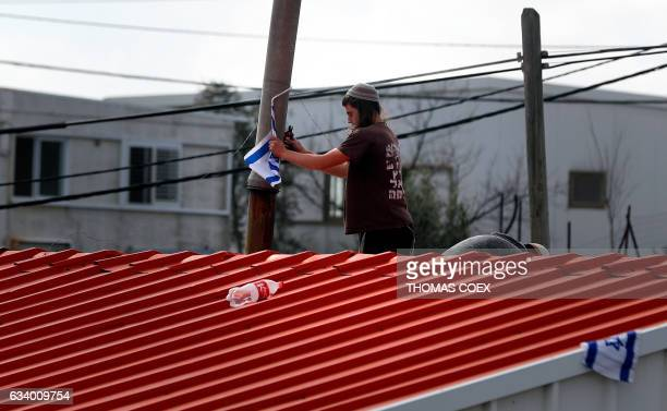 An Israeli settler removes the Israeli flag from the roof of a prefabricate house in the Israeli Amona wildcat outpost northeast of Ramallah in the...