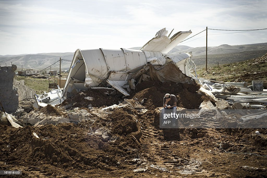 An Israeli settler sits praying among the rubble of his house that was demolished by Israeli police in the outpost of Maale Rehavam, in the Israeli occupied Palestinian West Bank, on February 13, 2013. The house was built without any authorization outside the larger state-sanctioned settlement. The number of Israeli settlers in the occupied West Bank grew by 4.7% in 2012, according to figures obtained by AFP from a settler organisation.