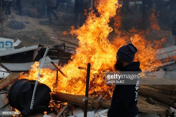 TOPSHOT An Israeli settler stands next to burning furniture during scuffle with security forces at the Amona outpost northeast of Ramallah on...