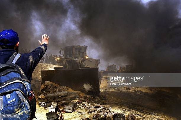 An Israeli settler tries to block an army bulldozer on February 1 2006 in the West Bank outpost of Amona The residents of Amona compose one of...