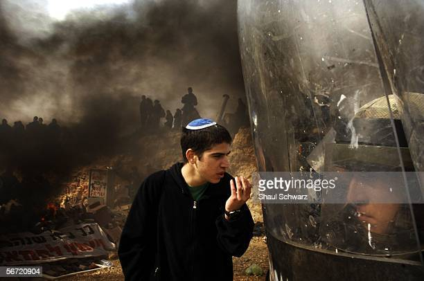 An Israeli settler tries to talk to Israeli riot police February 1 2006 in the West Bank outpost of Amona The residents of Amona compose one of...