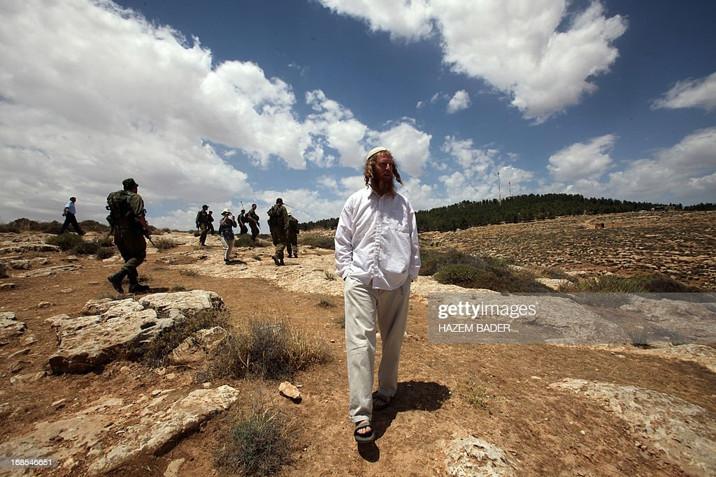 An Israeli settler walks near a land damaged by vandals the day before in the village of Al-Tiwana, south of the West Bank city of Hebron on May 11, 2013. Vandals believed to be Jewish extremists have uprooted dozens of olive trees and scrawled graffiti near a Palestinian village in the southern West Bank, police and witnesses said.