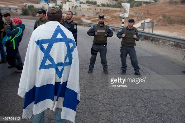 An Israeli settler with an Israeli flag stands next to Israeli policemen in a demonstration on October 7 2015 at the enterance to the village of Beit...