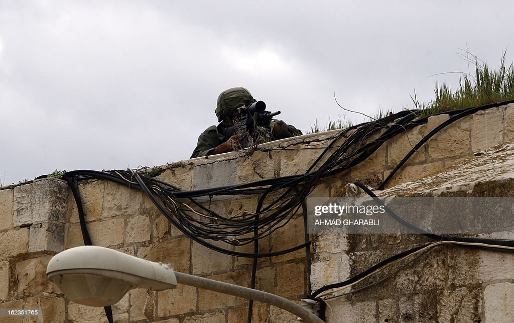 An Israeli soldier adjusts his scope during clashes with Palestinian demonstrators gathering in solidarity with hunger-striking Palestinian prisoners, at Jerusalem's Al-Aqsa mosque on February 22, 2013. Palestinians demanding the release of hunger-striking prisoners clashed with Israelis in the West Bank and east Jerusalem, as three fasting inmates were taken to hospitals.