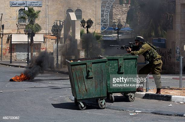 An Israeli soldier aims his gun during clashes with Palestinian stone throwers in the West Bank town of Hebron on June 16 2014 The Israeli army says...