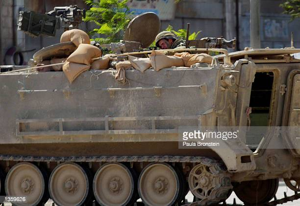 An Israeli soldier aims his gun from inside an armored tank during another day of Israeliimposed curfew August 29 2002 in Nablus West Bank Young...
