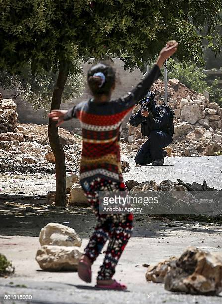 An Israeli soldier aims his weapon at a stonethrowing Palestinian girl during a demonstration against the expropriation of Palestinian land by Israel...