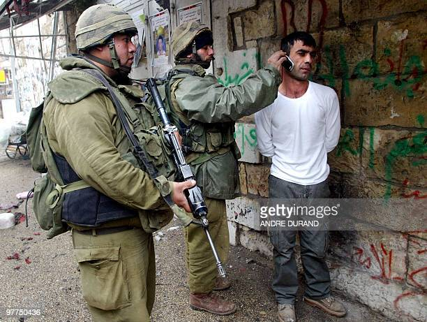 An Israeli soldier brings a mobile phone close to the ear of an arrested Palestinian man 30 March 2002 in the West Bank city of Ramallah following an...