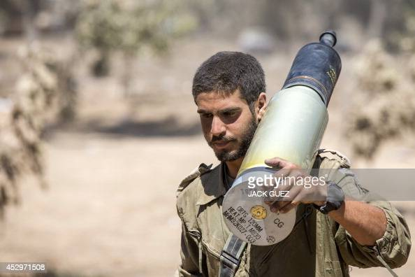 An Israeli soldier carries a shell as he and his comrades prepare their Merkava tanks stationed at an army deployment area along the border between...