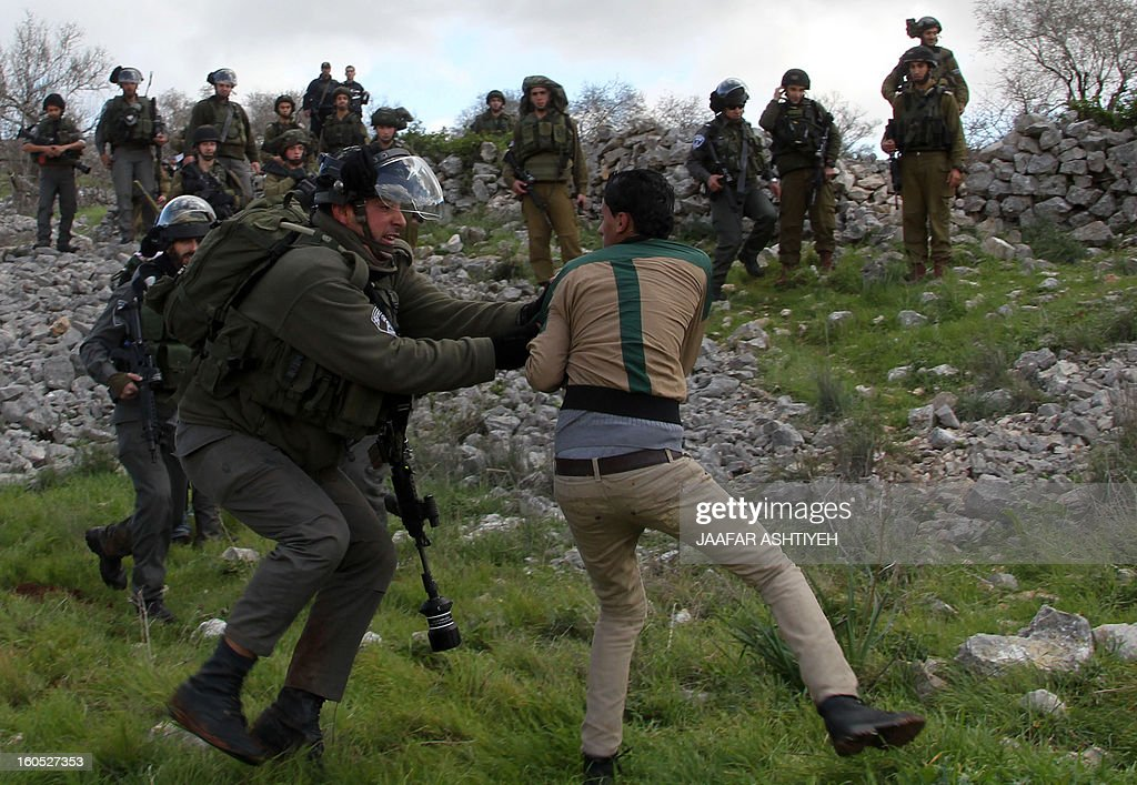 An Israeli soldier catches a Palestinian man as they forcefully remove demonstrators from a new camp set up to protest against Jewish settlements near the West Bank village of Burin on February 2, 2013. An AFP correspondent said the Israeli army used tear gas and violence to remove hundreds of people who had set up four temporary huts and three tents near Burin, south of Nablus in the occupied West Bank, in a third attempt at the novel form of protest against Jewish settlements. AFP PHOTO /JAAFAR ASHTIYEH